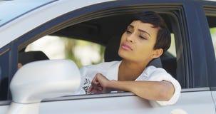 Schwarze Frau im Auto, das herum aus Fenster heraus schaut Stockbild