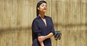 Schwarze Frau im Kleid, das an der Wand sich lehnt und Sonnenlicht genießt Stockfotografie