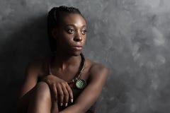 Schwarze Frau mit der ethnischen Halskette, die rechts schaut; Lizenzfreie Stockfotografie