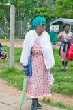Schwarze Frau mit grünem Regenschirm gehend durch Zulu- Dorf im Zululand, Südafrika Stockfoto