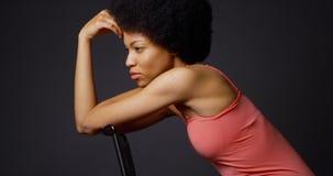 Schwarze Frau tief im Gedanken, der im Stuhl sitzt lizenzfreie stockfotografie