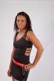 Schwarze Frau, welche die Kamera mit einem Lächeln betrachtet Lizenzfreie Stockbilder