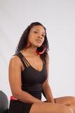 Schwarze Frau, welche die Kamera mit einem Lächeln betrachtet Stockfotografie