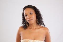 Schwarze Frau, welche die Kamera mit einem Lächeln betrachtet Stockbild
