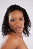 Schwarze Frau, welche die Kamera mit einem Lächeln betrachtet Lizenzfreie Stockfotografie