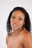 Schwarze Frau, welche die Kamera mit einem Lächeln betrachtet Stockbilder