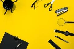Schwarze Gegenstände vom Büro auf einem gelben Hintergrund Arbeit und Kreativität Beschneidungspfad eingeschlossen lizenzfreies stockbild