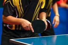 Schwarze gelbe Hemdmänner, die doppeltes Tischtennis spielen lizenzfreies stockfoto