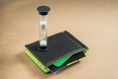 Schwarze Geldbörse mit Kreditkarten, grünes Innere Zeit ist Geld Stockfoto
