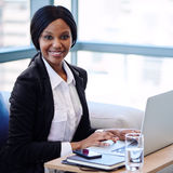 Schwarze Geschäftsfrau, die an der Kamera vor Computer lächelt Stockbild
