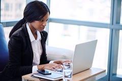 Schwarze Geschäftsfrau, die an ihrem Notizbuch in einem Geschäftsaufenthaltsraum arbeitet Stockbild