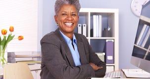 Schwarze Geschäftsfrau, die am Schreibtischlächeln sitzt Lizenzfreies Stockfoto