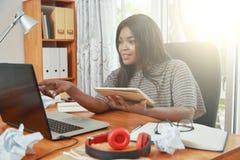 Schwarze Geschäftsfrau, die Tablette und Laptop im Büro verwendet lizenzfreie stockfotos