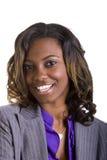 Schwarze Geschäftsfrau im graue Klage-großen Lächeln stockbild
