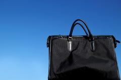 Schwarze Geschäftstasche im blauen Himmel Lizenzfreie Stockbilder