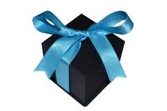 Schwarze Geschenkbox mit blauem Band auf weißem Hintergrund Stockbild