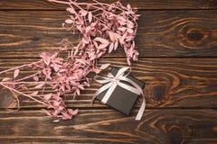 Schwarze Geschenkbox mit einem Bogen ist auf dem Baum und den nahen Blumen Lizenzfreie Stockfotografie