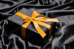 Schwarze Geschenkbox mit gelbem Satinband Lizenzfreies Stockbild