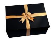 Schwarze Geschenkbox mit Goldband und Bogen lokalisiert auf Weiß (Beschneidungspfad) Lizenzfreies Stockfoto