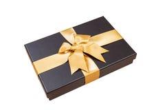 Schwarze Geschenkbox mit Goldband und ein Bogen auf weißem Hintergrund Lizenzfreie Stockbilder