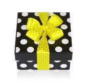 Schwarze Geschenkbox mit weißen Tupfen mit gelbem Bogen Stockbilder