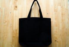 Schwarze Gewebetasche auf hölzernem Hintergrund stockfotos