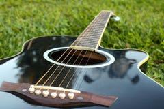 Schwarze Gitarre, die auf dem gr?nen Rasen mit einem Fokus auf den Schn?ren liegt stockfotos