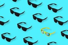 Schwarze Gläser auf blauem Pastellhintergrund Unter den vielen schwarzen Gläsern allein gelb minimales Sommerkonzept lizenzfreie stockfotografie
