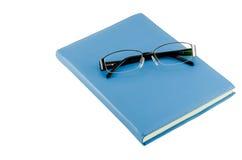 Schwarze Gläser auf blauem Tagebuch Stockfotografie