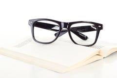 Schwarze Gläser auf offenem Buch Stockfotografie