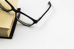 Schwarze Gläser und Buch Lizenzfreie Stockfotografie