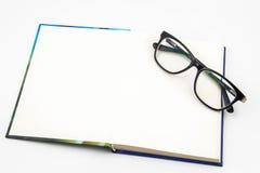 Schwarze Gläser und Buch Lizenzfreies Stockbild