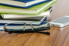 Schwarze Gläser und Stapel von Büchern stockfotografie