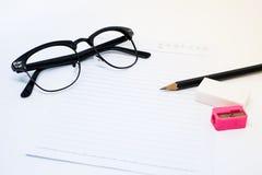 Schwarze Gläser, Weißbuch, Bleistift, rosa Bleistiftspitzer und Radiergummi Lizenzfreie Stockfotos