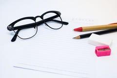 Schwarze Gläser, Weißbuch, Bleistift, Stift, rosa Bleistiftspitzer Stockfotos