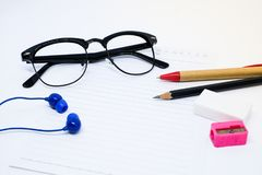 Schwarze Gläser, Weißbuch, Bleistift, Stift, rosa Bleistiftspitzer, Radiergummi Stockfoto