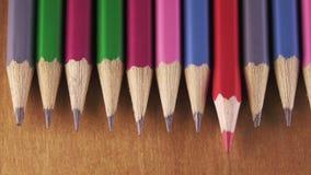 Schwarze grafische Bleistifte und roter Bleistift liegen in Folge auf einer Holzoberfläche stock video footage