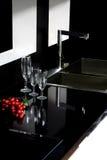 Schwarze Granitoberseite mit glänzenden Gläsern Stockfotografie