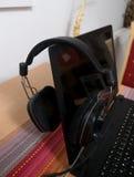 Schwarze große DJ-Kopfhörer verließen auf dem Laptop nach mischender Musik Lizenzfreies Stockbild