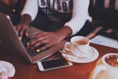Schwarze Hände mit varicoloured Nägeln auf Laptoptastatur im Café lizenzfreie stockfotografie
