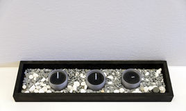Schwarze hölzerne Servierplatte mit drei schwarzen Teelichtern Stockfotos