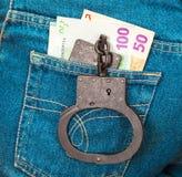 Schwarze Handschellen der Polizei Metallund Eurowährung Stockbilder