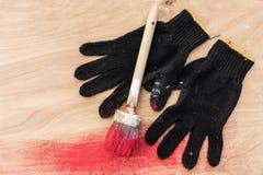 Schwarze Handschuhe befleckten in der Farbe, eine Bürste in der roten Farbe, Lüge auf Sperrholz Stockfoto