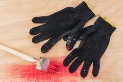 Schwarze Handschuhe befleckten in der Farbe, eine Bürste in der roten Farbe, Lüge auf Sperrholz Stockbilder