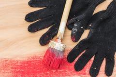 Schwarze Handschuhe befleckten in der Farbe, eine Bürste in der roten Farbe, Lüge auf Sperrholz Lizenzfreie Stockfotos