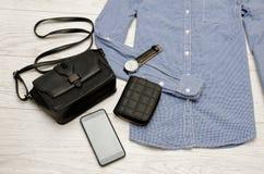 Schwarze Handtasche, Handy, Geldbeutel und eine Uhr im blauen Hemd Art und Weisekonzept Stockbild