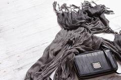 Schwarze Handtasche und moderner grauer Schal Stockfoto