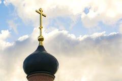 Schwarze Haube der Kirche mit einem goldenen Kreuz auf dem Himmelhintergrund mit weißen Wolken Turm des alten roten Backsteins an Stockfotos
