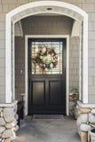 Schwarze Haustür eines Hauses gesehen durch einen Bogen Lizenzfreie Stockfotos