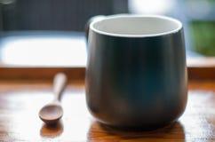 Schwarze heiße EspressoKaffeetasse wird zusammen mit braunem Holz gesetzt stockfoto